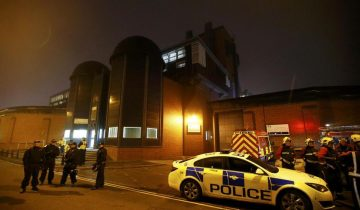 Police officers and firemen stand outside Winson Green prison, run by security firm G4S, after a serious disturbance broke out, in Birmingham