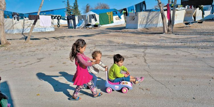 Afghan refugee children play at the refugee camp of Oinofyta about 58 kilometers (36 miles) north of Athens, Monday, Jan. 2, 2017. Over 62,000 refugees and migrants are stranded in Greece after a series of Balkan border closures and an European Union deal with Turkey to stop migrant flows. (AP Photo/Muhammed Muheisen)