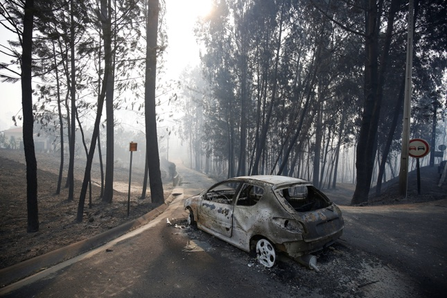 A burned car is seen in the aftermath of a forest fire near Pedrogao Grande, in central Portugal, June 18, 2017. REUTERS/Rafael Marchante TPX IMAGES OF THE DAY