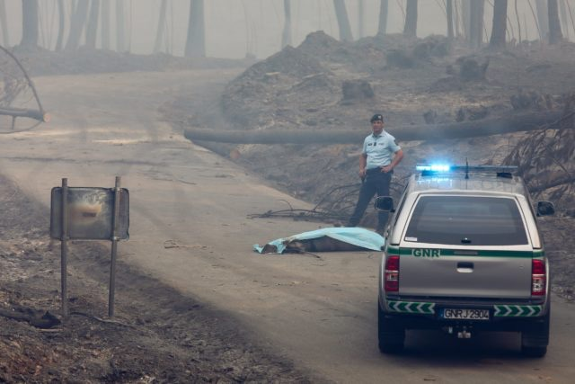 epaselect epa06034888 A Republican National Guard member stays near a unidentified dead body, near the IC8 road beteew Avelar and Pedrogao Grande, central Portugal, 18 June 2017. At least fifty-seven people have been killed in forest fires in central Portugal, with many being trapped in their cars as flames swept over a road on the evening of 17 June 2017. A total of 688 firefighters are providing assistance. EPA/MIGUEL A. LOPES