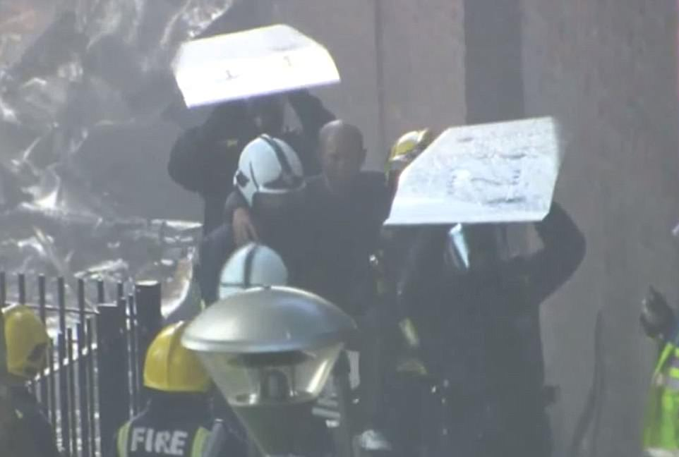 The moment a resident is carried out of the Grenfell Tower block by fire bridgae and riot police carrying shield