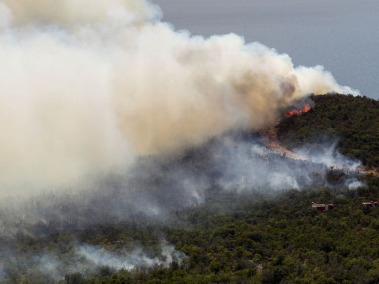 Firefighters try to control a forest fire at Lustica peninsula near Tivat