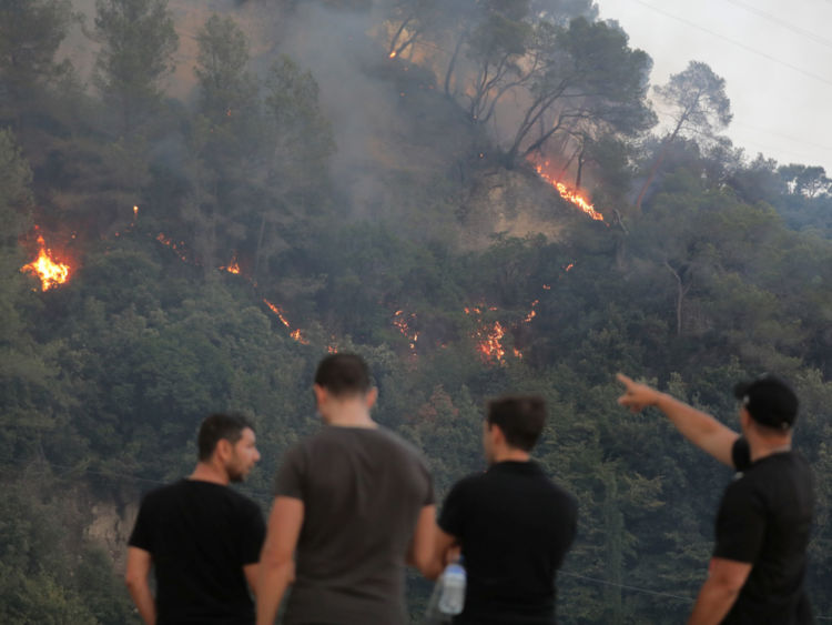 People look at a forest fire in Castagniers near Nice