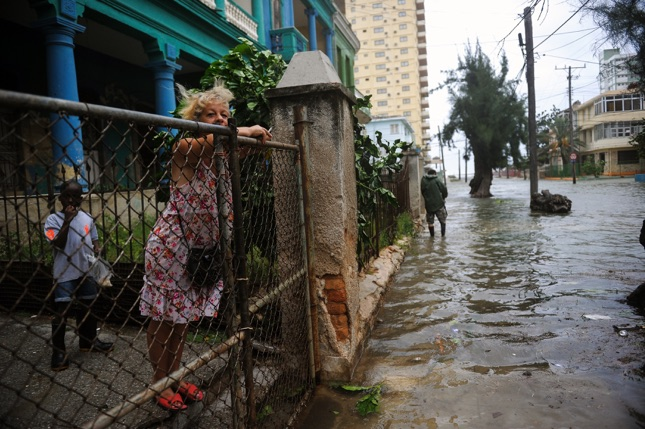 A woman looks at a flooded street during the passage of Hurricane Irma in Havana, on September 9, 2017.  Irma's blast through the Cuban coastline weakened it to a Category Three, but it is still packing winds of 125 miles (200 kilometer) per hour. / AFP PHOTO / YAMIL LAGE