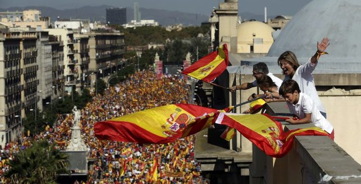 People on a rooftop wave Spanish flags during a march in downtown Barcelona, Spain, to protest the Catalan government's push for secession from the rest of Spain, Sunday Oct. 8, 2017. Sunday's rally comes a week after separatist leaders of the Catalan government held a referendum on secession that Spain's top court had suspended and the Spanish government said was illegal. (AP Photo/Manu Fernandez)