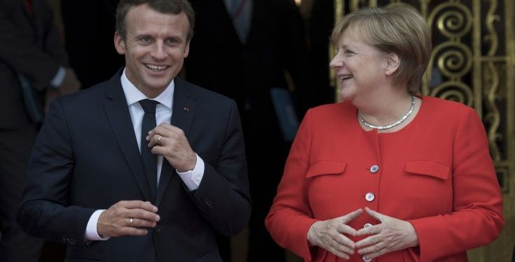 French president Emmanuel Macron, left, and German chancellor Angela Merkel meet ahead of the opening of the Frankfurt Book Fair in Frankfurt am Main, Germany, Tuesday, Oct. 10, 2017. France is this year's honorary guest. (Boris Roessler/dpa via AP)