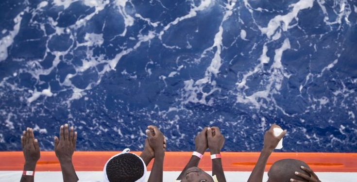 "African migrants stand on the deck of the Aquarius vessel of ""SOS Mediterranee"" and MSF (Doctors Without Borders) NGOs, in the Mediterranean Sea, southwest of Malta, Thursday, Aug. 31, 2017. 265 people rescued from the sea during previous days are being transferred to Italy. (AP Photo/Darko Bandic)"