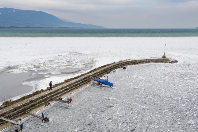 epa06570886 A picture taken with a drone shows a man walking next to a boat surrounded by ice on the frozen shore of the Lake of Neuchatel, in Yverdon-les-Bains, Switzerland, 28 February 2018. Media reports on 26 February stated that extreme cold weather is forecast to hit many parts of Europe with temperatures plummeting to a possible ten year low.  EPA/VALENTIN FLAURAUD