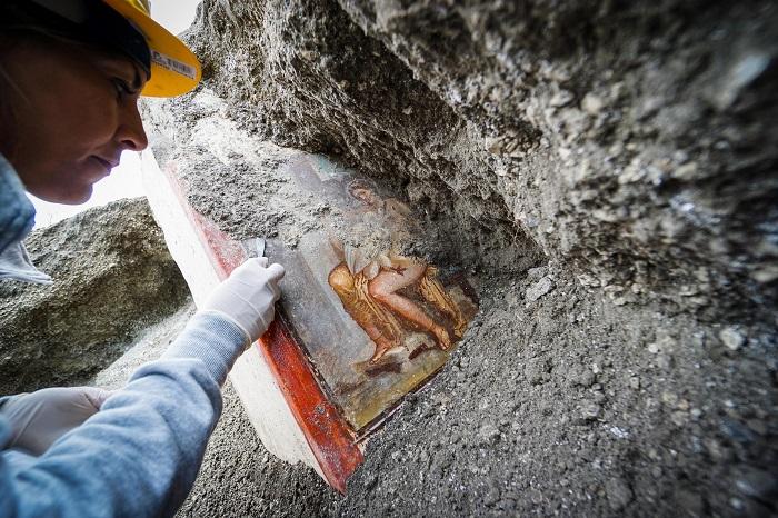 An archelogist works on the fresco ''Leda e il cigno'' in Pompeii