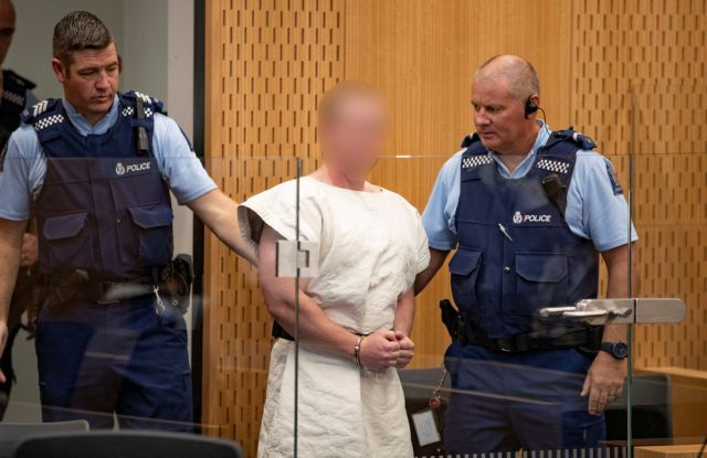 Brenton Tarrant, charged for murder in relation to the mosque attacks, is lead into the dock for his appearance in the Christchurch District Court
