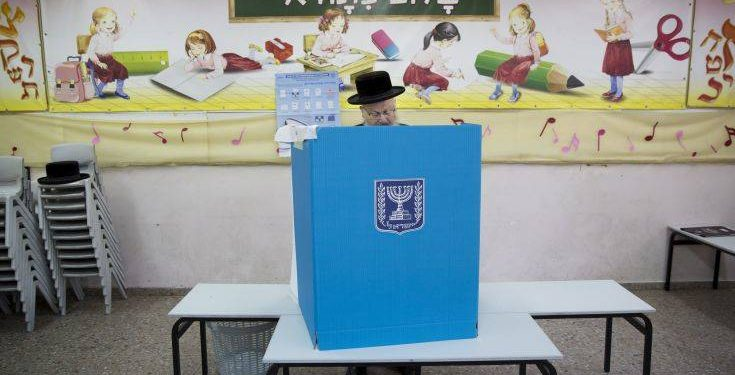 An ultra-Orthodox Jewish man votes for Israel's parliamentary election at a polling station in Bnei Brak, Israel, Tuesday, April 9, 2019. (AP Photo/Oded Balilty)