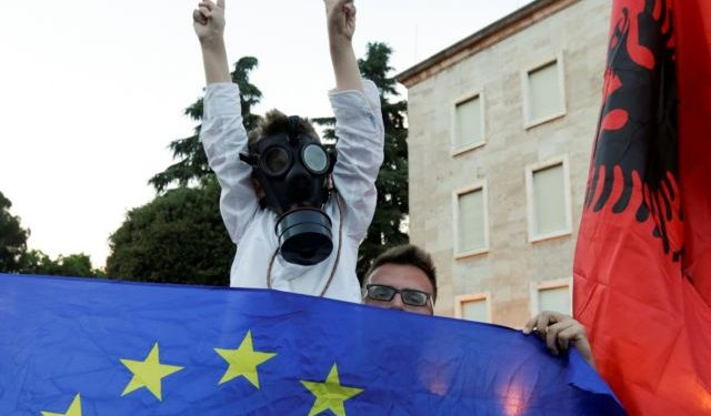 A child wearing a gask mask attends an anti-government protest, calling on Prime Minister Edi Rama to step down, in Tirana