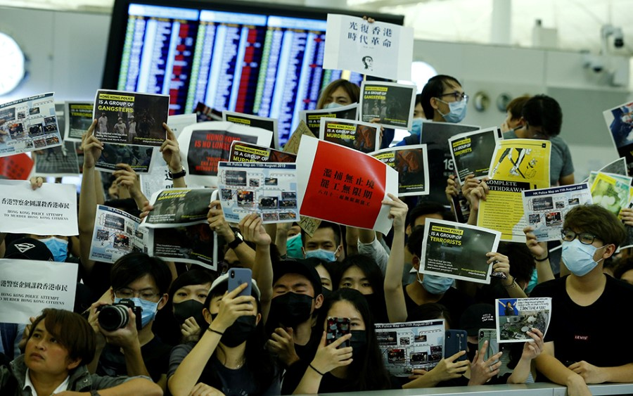 Anti-government protesters gesture at police during clashes at the airport in Hong Kong