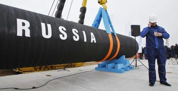 FILE In this Friday, April 9, 2010 file photo a Russian construction worker speaks on a mobile phone in Portovaya Bay some 170 kms (106 miles) north-west from St. Petersburg, Russia, during a ceremony marking the start of Nord Stream pipeline construction. Wednesday's decision by the Danish Energy Agency to approve the Nord Stream 2 pipeline's route is a blow to the U.S. President Donald Trump's administration, which had fiercely opposed it, and a victory for Russia and Germany which staunchly supported it.  (AP Photo/Dmitry Lovetsky, file)