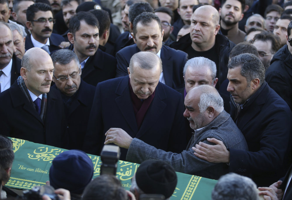 Turkey's President Recep Tayyip Erdogan, centre, comforts relatives of a victim after an earthquake hit Elazig, eastern Turkey, Friday, during the funeral procession for Salih Civelek and Aysegul Civelek, Saturday, Jan. 25, 2020. Rescuers continued searching for people buried under the rubble of collapsed buildings while emergency workers and security forces distributed tents, beds and blankets in the affected areas. Mosques, schools, sports halls and student dormitories were opened for hundreds who left their homes after the quake. (Presidential Press Service via AP, Pool)