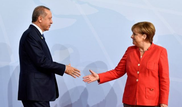 FILE PHOTO: German Chancellor Angela Merkel greets Turkey's President Recep Tayyip Erdogan at the beginning of the G20 summit in Hamburg, Germany, July 7, 2017. REUTERS/John MACDOUGALL/POOL/File Photo