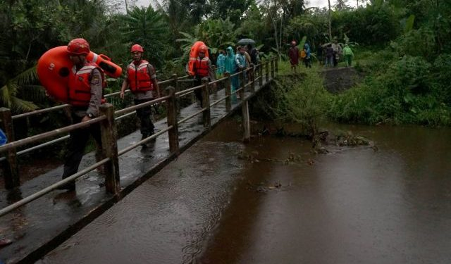 Rescue workers walk past a bridge as they search for students who were missing after a tidal surge swept them away during a school trip, in Sleman