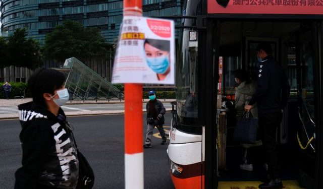 Passengers wear mask at a bus stop, following the coronavirus outbreak in Macau