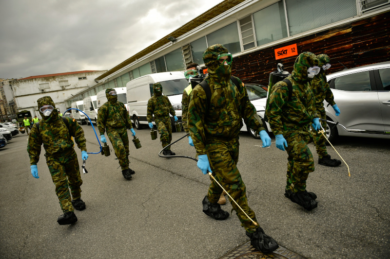 Member of Military Emergency Unit walk with special equipment to disinfect areas to prevent the spread of the coronavirus, arrive at Abando train station, in Bilbao, northern Spain, Monday, March 23, 2020. For some people the COVID-19 coronavirus causes mild or moderate symptoms, but for some it causes severe illness. (AP Photo/Alvaro Barrientos)