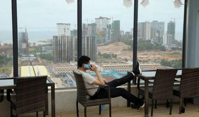 """A man speaks on his phone on the rooftop of Chinese businessman Kang Quiang's casino Dong Yuan, in Sihanoukville, Cambodia, February 28, 2020. REUTERS/Jorge Silva     SEARCH """"COVID-19 CAMBODIA CASINOS"""" FOR THIS STORY. SEARCH """"WIDER IMAGE"""" FOR ALL STORIES."""