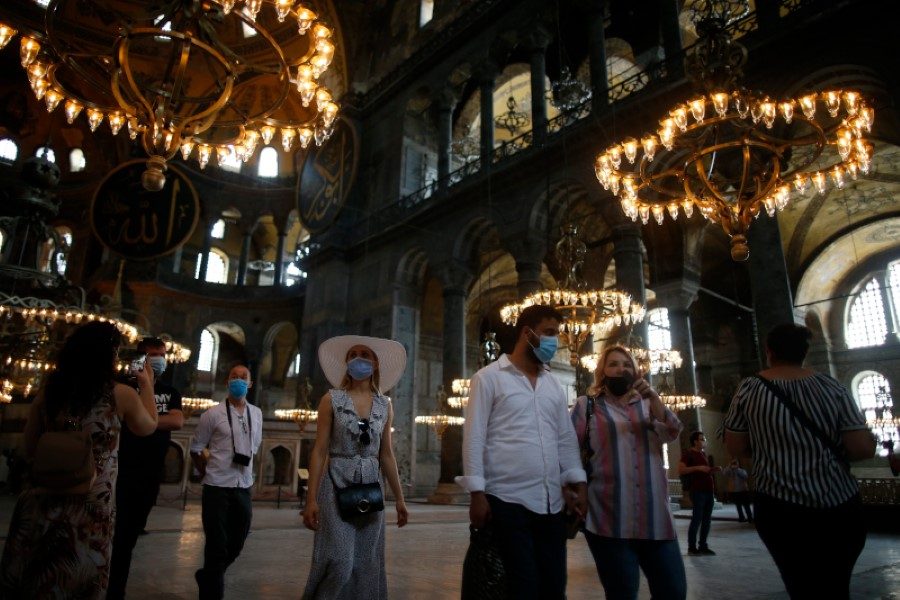 People visit the Byzantine-era Hagia Sophia, an UNESCO World Heritage site and one of Istanbul's main tourist attractions in the historic Sultanahmet district of Istanbul, Friday, July 10, 2020. Turkey's highest administrative court issued a ruling Friday that paves the way for the government to convert Hagia Sophia - a former cathedral-turned-mosque that now serves as a museum - back into a Muslim house of worship. The Council of State threw its weight behind a petition brought by a religious group and annulled a 1934 cabinet decision that changed the 6th century building into a museum. (AP Photo/Emrah Gurel)