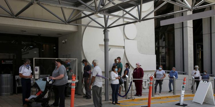 People wait for health assessment check-in before entering Jackson Memorial Hospital, as Miami-Dade County eases some of the lockdown measures put in place during the coronavirus disease (COVID-19) outbreak, in Miami, Florida, U.S., June 18, 2020. REUTERS/Marco Bello