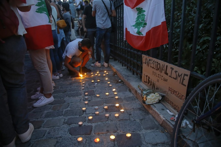 A man of the Lebanese community lights a candle next to a Lebanese flag during a vigil in memory of victims of the deadly blast in Beirut in Paris, Wednesday, Aug. 5, 2020. French President Emmanuel Macron is traveling to Lebanon on Thursday to offer support for the country after a massive, deadly explosion. (AP Photo/Michel Euler)