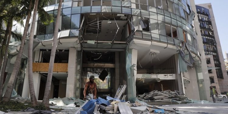 A worker removes broken windows and debris from one of damaged streets, after an explosion hit the seaport of Beirut, Lebanon, Wednesday, Aug. 5, 2020. Residents of Beirut awoke to a scene of utter devastation on Wednesday, a day after a massive explosion at the port sent shock waves across the Lebanese capital, killing at least 100 people and wounding thousands. (AP Photo/Hussein Malla)