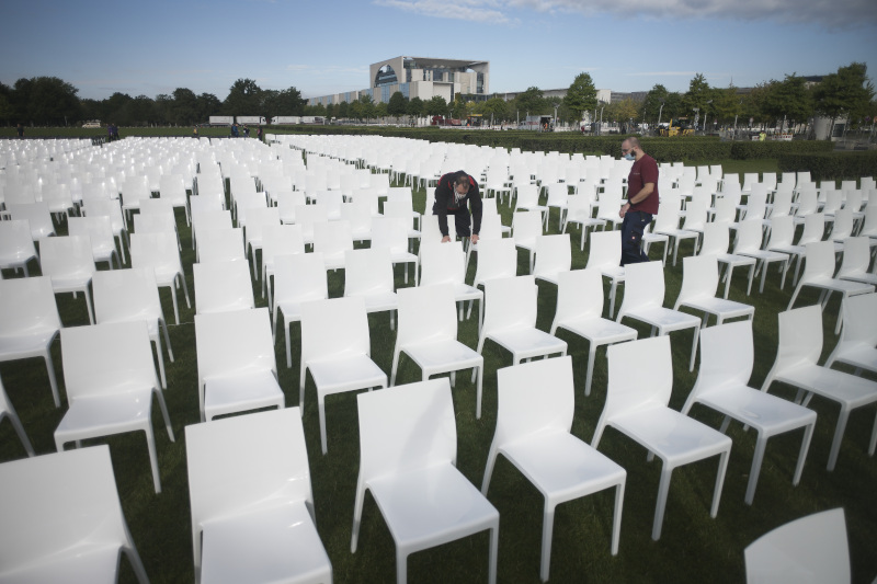 Activists set up chairs at the 'Platz der Republik' in with the chancellery in the background, as part of the nationwide anti-racist action days of 'We'll Come United' in Berlin, Germany, Monday, Sept. 7, 2020. About some 13.000 chairs will be placed here in front of the parliament building, symbolising the people who currently live in Moria migrants camp in Greece. (AP Photo/Markus Schreiber)