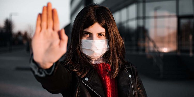 Young girl shows hand sign stop no to coronavirus epidemic pandemia originated at China. Covid-19 virus, nCov2019. Girl is against using public transport and stay home during quarantine