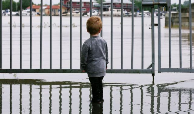 A child looks on as water floods through a fence, in Wessem